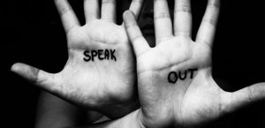 Hands with writing on them saying speak out